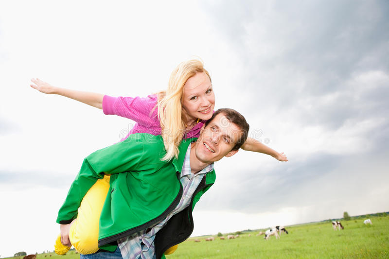 Pares novos do amor que sorriem sob o céu azul foto de stock royalty free