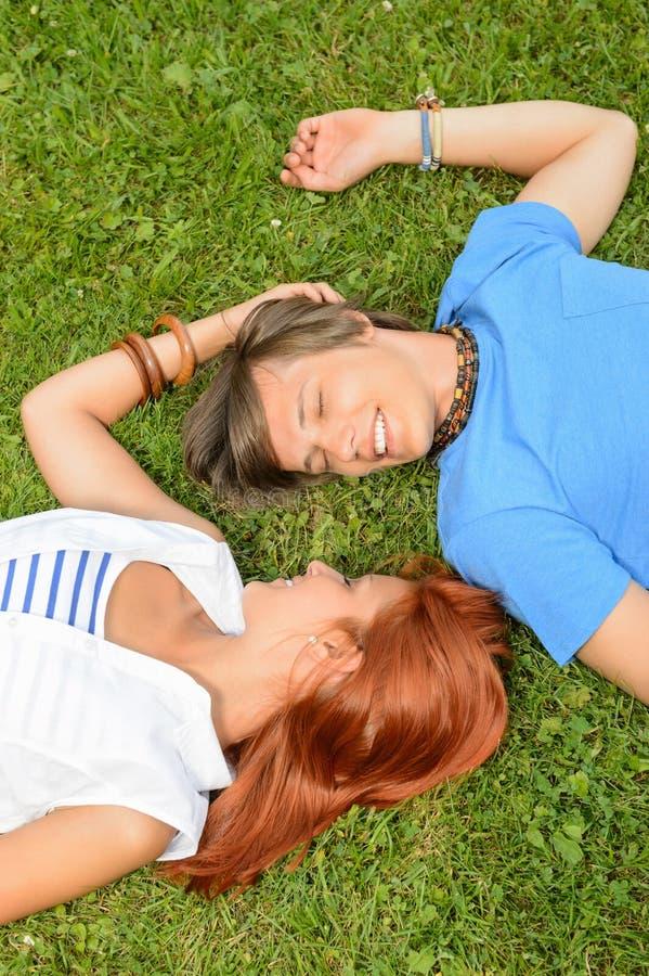 Pares novos do amor romântico que encontram-se na grama foto de stock