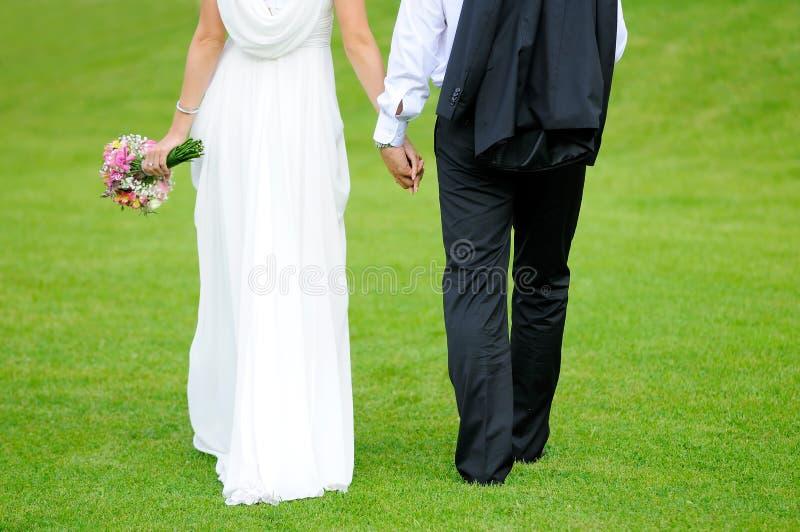 Pares novos do casamento no prado imagens de stock royalty free