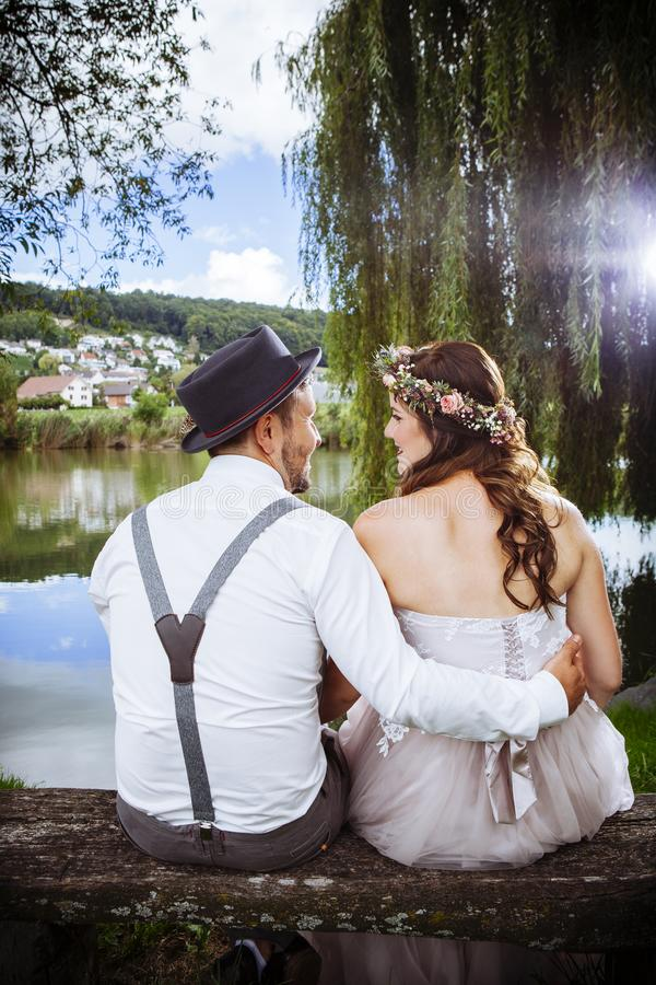 Pares novos do casamento que sentam-se em um banco imagens de stock