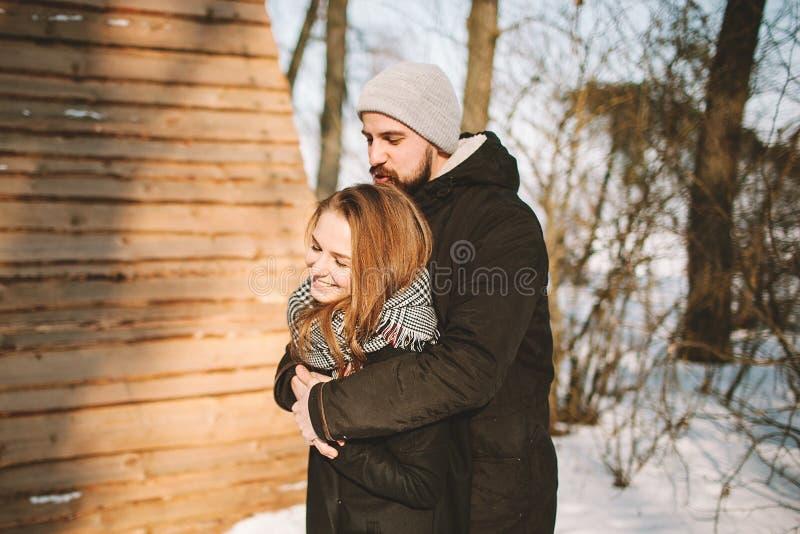 Pares novos do moderno que abraçam na floresta do inverno imagens de stock