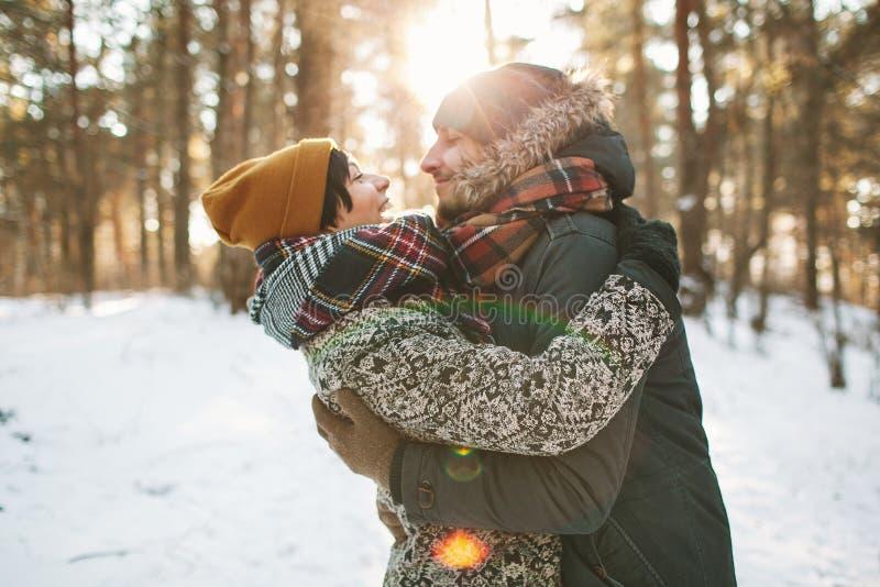 Pares novos do moderno que abraçam-se na floresta do inverno fotos de stock royalty free