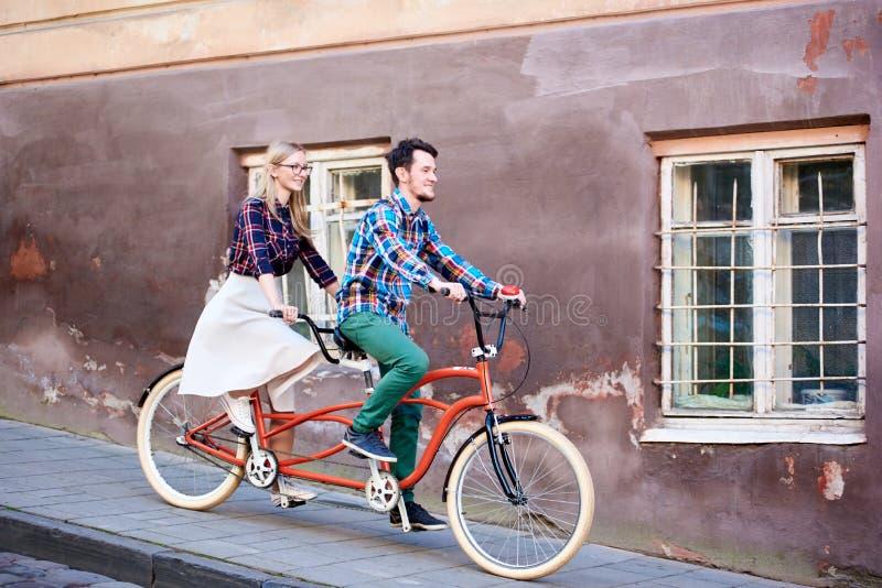 Pares novos do turista, homem considerável e mulher consideravelmente loura montando a bicicleta em tandem ao longo da rua da cid imagens de stock