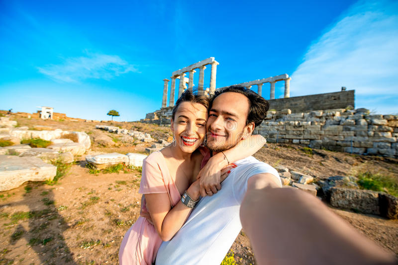 Pares novos do turista perto do templo de Poseidon em Grécia fotos de stock royalty free