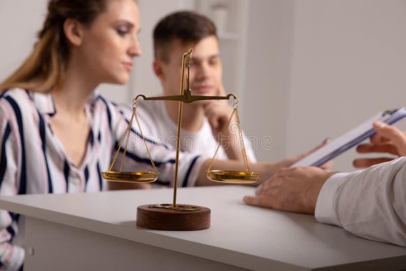 Pares novos dos renters que sentam-se no sofá que discute alugando o apartamento com o mediador imobiliário, foco no acordo aluga imagens de stock