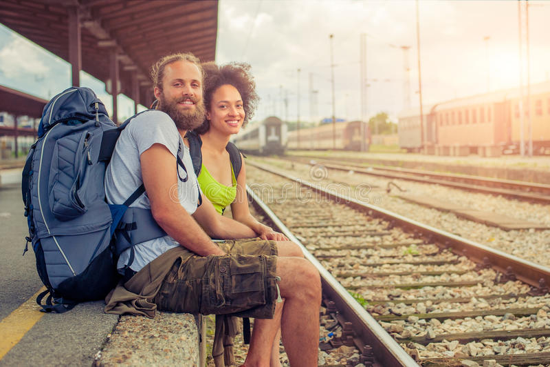 Pares novos e bonitos felizes de turistas que sentam-se no trilho imagem de stock