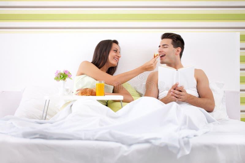 Pares novos e bonitos que comem o café da manhã na cama imagens de stock