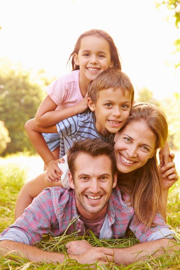 Pares novos e crianças que têm o divertimento junto fora imagens de stock