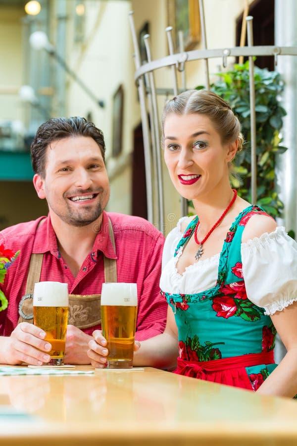 Pares novos em Baviera no restaurante ou no bar fotografia de stock