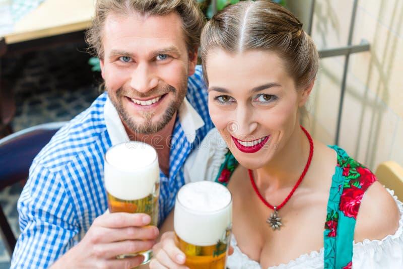 Pares novos em Baviera no restaurante ou no bar foto de stock royalty free