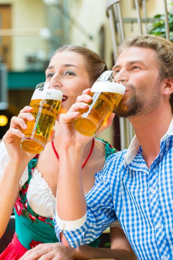 Pares novos em Baviera no restaurante ou no bar imagem de stock