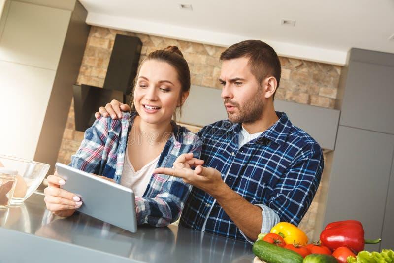 Pares novos em casa que estão no marido da cozinha junto que abraça a esposa que guarda a tabuleta digital que pergunta lhe sobre foto de stock