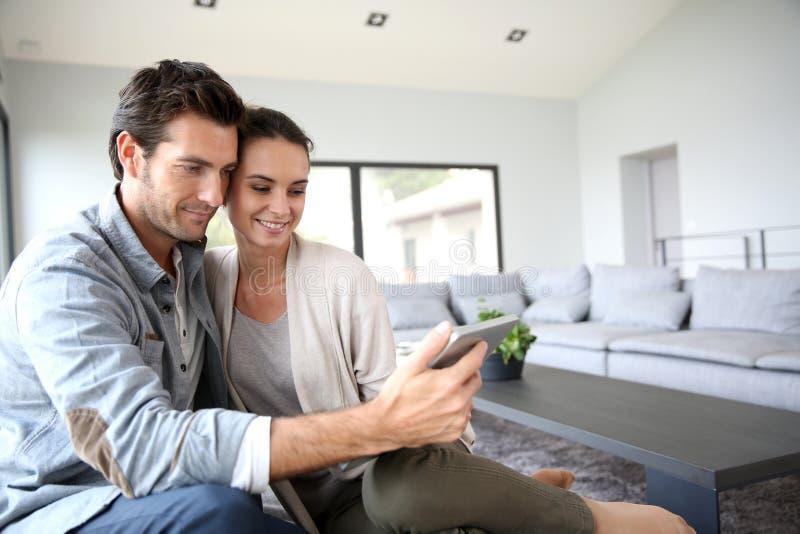 Pares novos em casa que usam a tabuleta fotografia de stock
