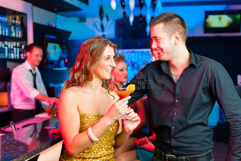 Pares novos em cocktail bebendo da barra ou do clube imagens de stock