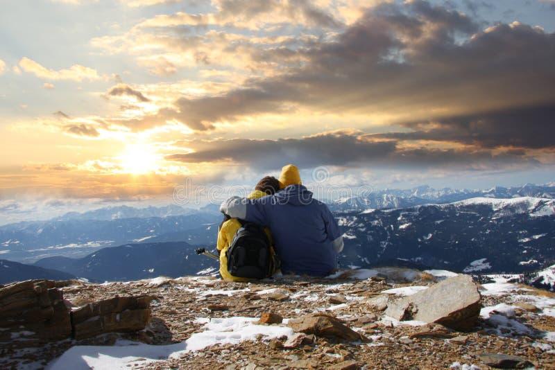 Pares novos em montanhas da neve imagem de stock royalty free