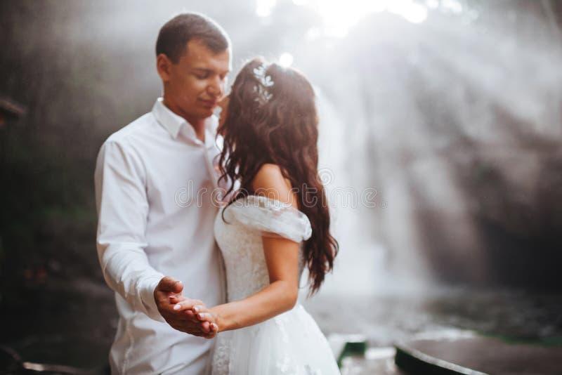 Pares novos em noivos do amor, dia do casamento perto de uma cachoeira da montanha imagens de stock royalty free