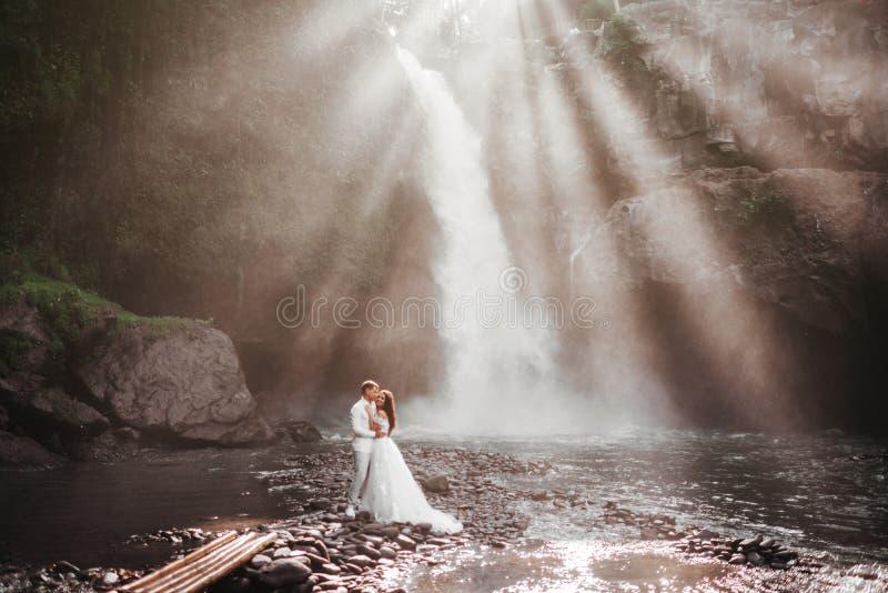 Pares novos em noivos do amor, dia do casamento perto de uma cachoeira da montanha fotografia de stock royalty free