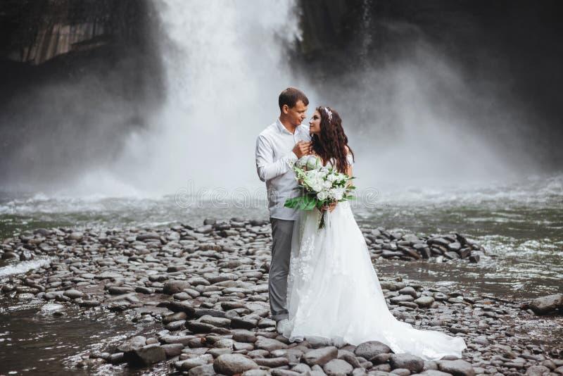 Pares novos em noivos do amor, dia do casamento perto de uma cachoeira da montanha foto de stock royalty free