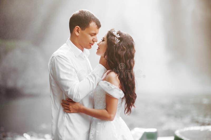 Pares novos em noivos do amor, dia do casamento perto de uma cachoeira da montanha fotos de stock