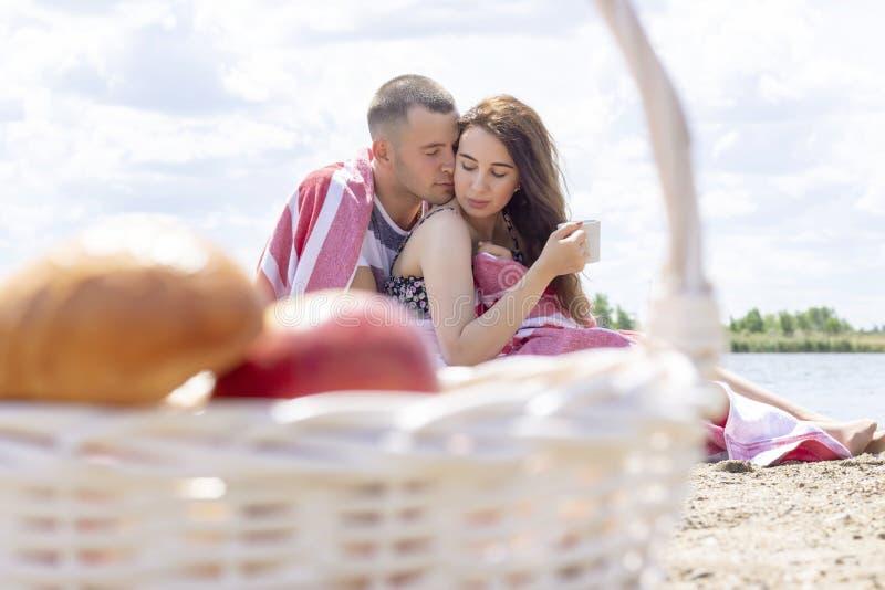Pares novos em um piquenique no mar, descanso do verão envolvido na cobertura piquenique do verão, reunião, amor fotografia de stock