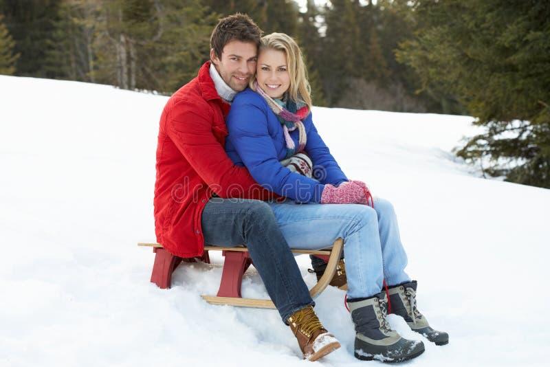 Pares novos em um trenó na cena alpina da neve foto de stock royalty free