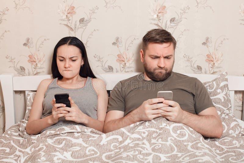 Pares novos em uma cama com telefones celulares foto de stock royalty free