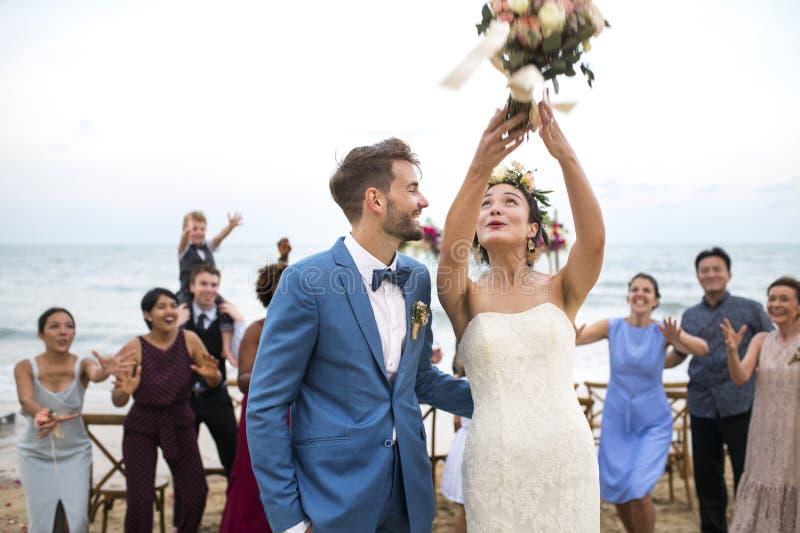 Pares novos em uma cerimônia de casamento na praia imagem de stock