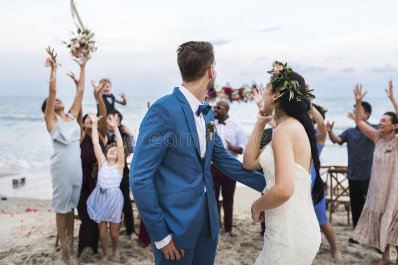 Pares novos em uma cerimônia de casamento na praia fotografia de stock royalty free