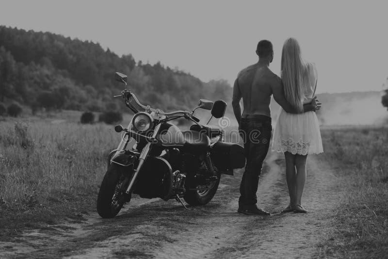 Pares novos em uma motocicleta no campo fotografia de stock