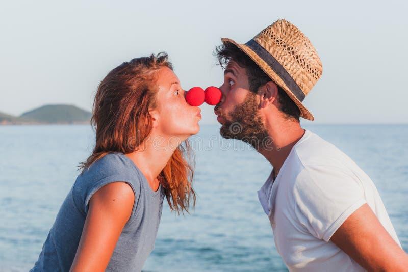 Pares novos engraçados no amor na praia imagens de stock