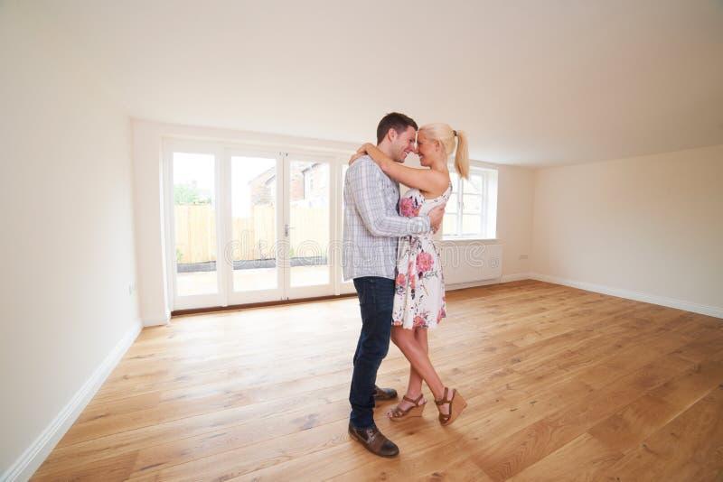 Pares novos entusiasmado na sala vazia da casa nova fotografia de stock royalty free