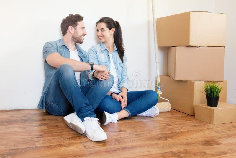 Pares novos entusiasmado que olham para a frente a mover-se em uma casa nova foto de stock royalty free