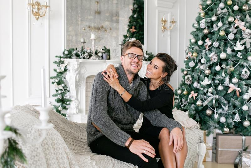 Pares novos Família feliz que tem o divertimento em casa Manhã de Natal na sala de visitas brilhante Ano novo feliz decorado fotografia de stock royalty free