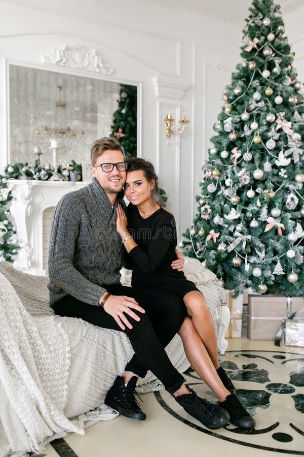 Pares novos Família feliz que tem o divertimento em casa Manhã de Natal na sala de visitas brilhante Ano novo feliz decorado fotos de stock royalty free