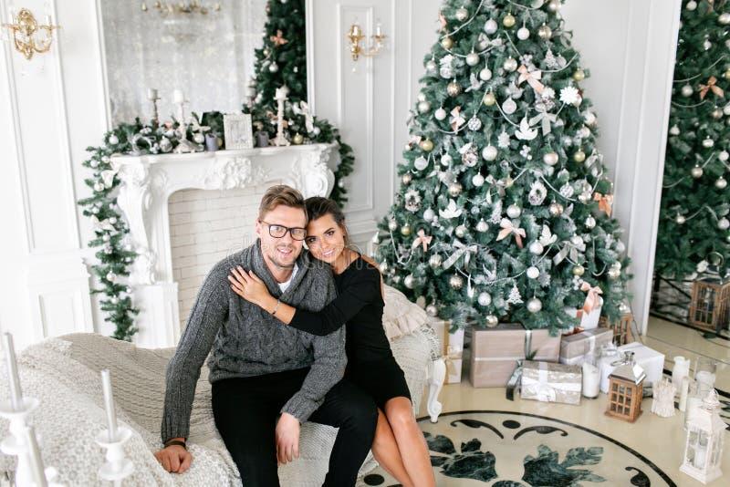 Pares novos Família feliz que tem o divertimento em casa Manhã de Natal na sala de visitas brilhante Ano novo feliz decorado fotos de stock