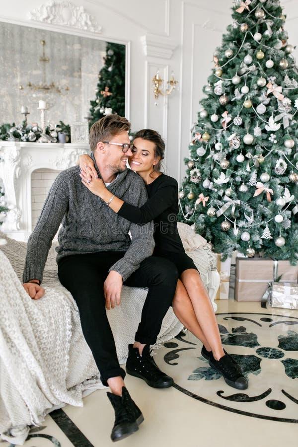 Pares novos Família feliz que tem o divertimento em casa Manhã de Natal na sala de visitas brilhante Ano novo feliz decorado fotografia de stock