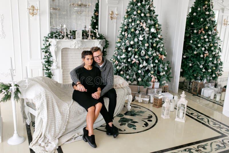 Pares novos Família feliz que tem o divertimento em casa Manhã de Natal na sala de visitas brilhante Ano novo feliz decorado foto de stock