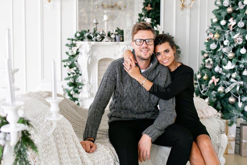 Pares novos Família feliz que tem o divertimento em casa Manhã de Natal na sala de visitas brilhante Ano novo feliz decorado imagens de stock royalty free