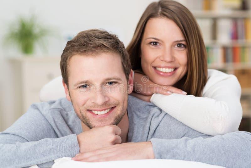 Pares novos felizes atrativos em sua sala de visitas imagens de stock royalty free
