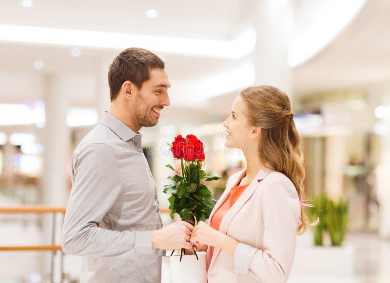 Pares novos felizes com as flores na alameda imagem de stock
