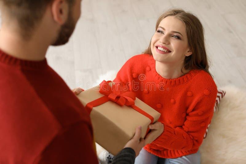 Pares novos felizes com caixa de presente do Natal fotografia de stock