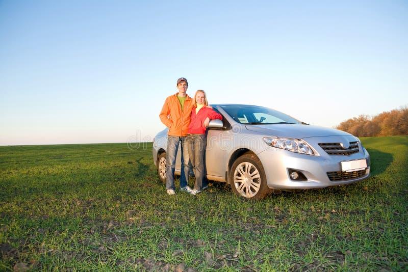 Pares novos felizes com carro novo foto de stock royalty free