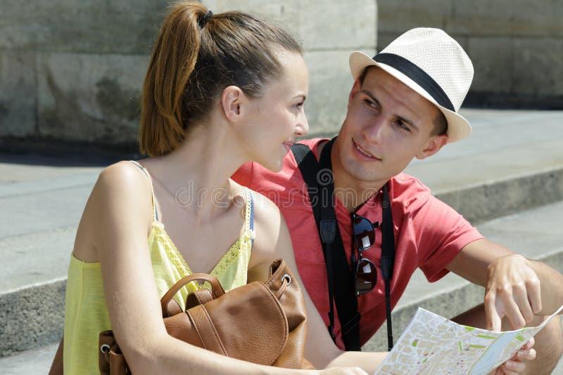 Pares novos felizes com a cidade do mapa do turista imagens de stock royalty free