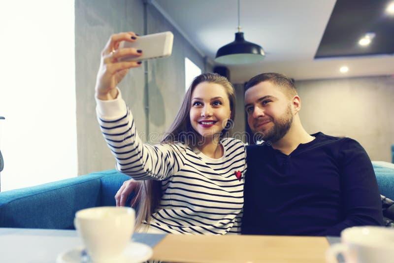 Pares novos felizes com o smartphone que toma o selfie no café na alameda venda, compra, consumição, tecnologia e povos imagens de stock