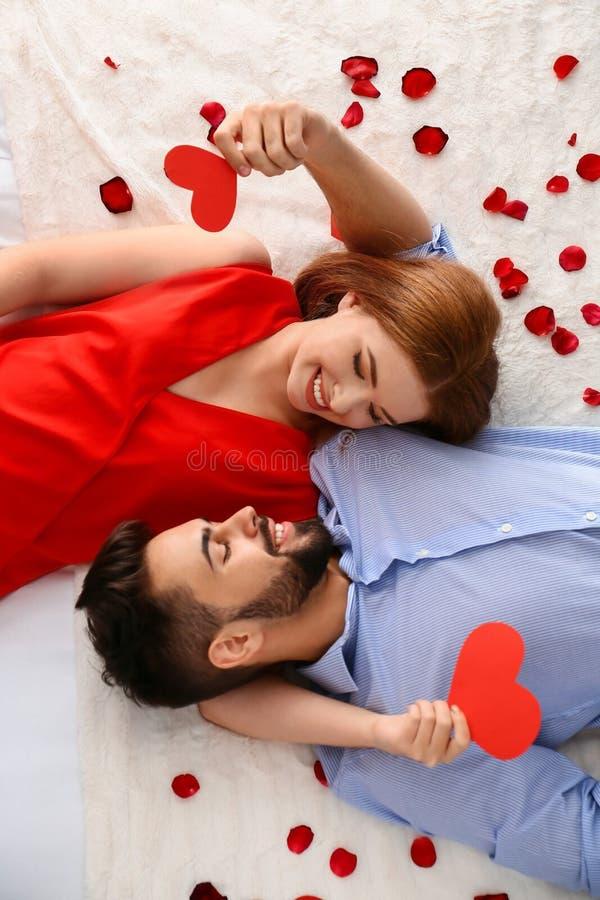 Pares novos felizes com os corações vermelhos que encontram-se na cama em casa Celebração do dia de Valentim de Saint foto de stock