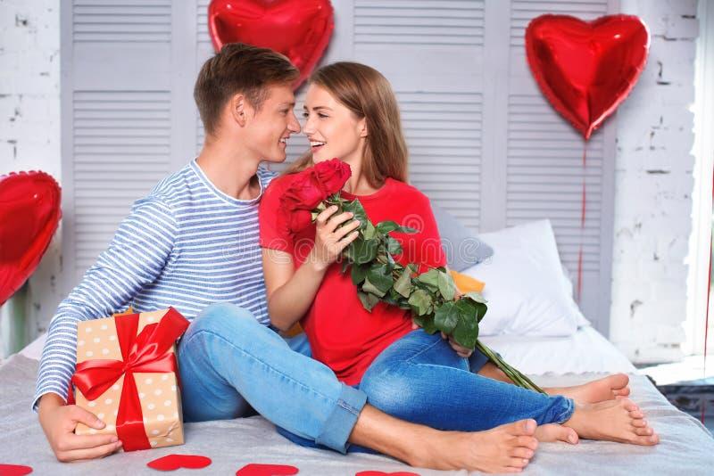 Pares novos felizes com rosas vermelhas e caixa de presente que sentam-se na cama em casa fotos de stock royalty free