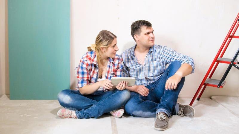 Pares novos felizes com a tabuleta digital que escolhe a mobília nova para sua casa fotografia de stock
