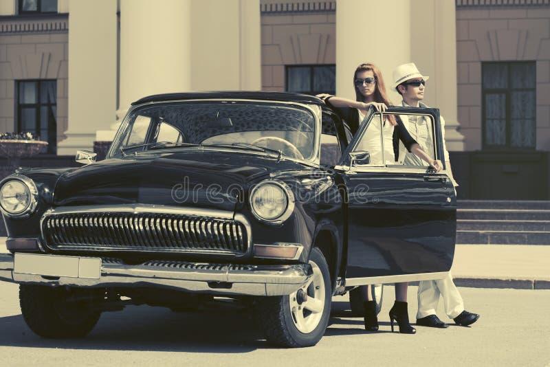 Pares novos felizes da forma no amor fora de um carro do vintage foto de stock