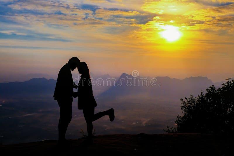 Pares novos felizes da silhueta no amor que olha o por do sol da vista na montanha Pares românticos no amor foto de stock royalty free