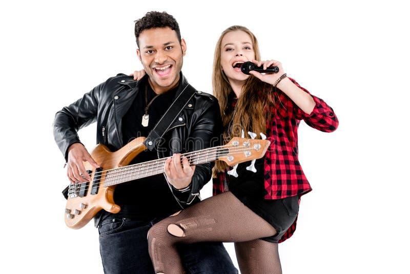 Pares novos felizes de músicos com o microfone e a guitarra elétrica que executam a música junto foto de stock